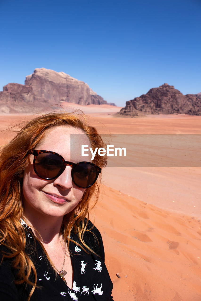 sunglasses, glasses, fashion, portrait, one person, sky, smiling, lifestyles, leisure activity, desert, sunlight, real people, scenics - nature, nature, mid adult, adult, women, mid adult women, beauty in nature, arid climate, climate, hairstyle, outdoors