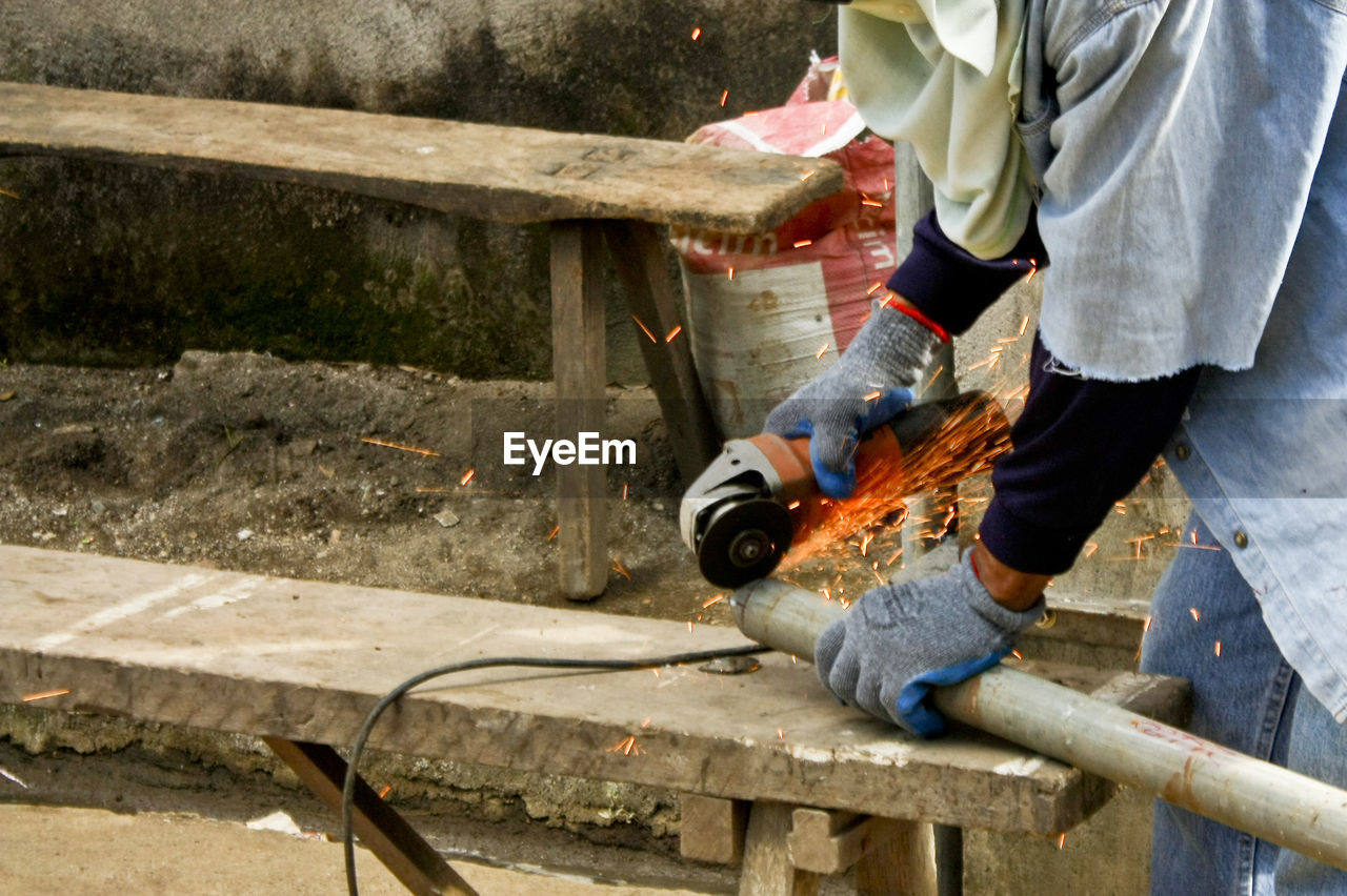 Cropped image of man working with polishing machine on wooden pole