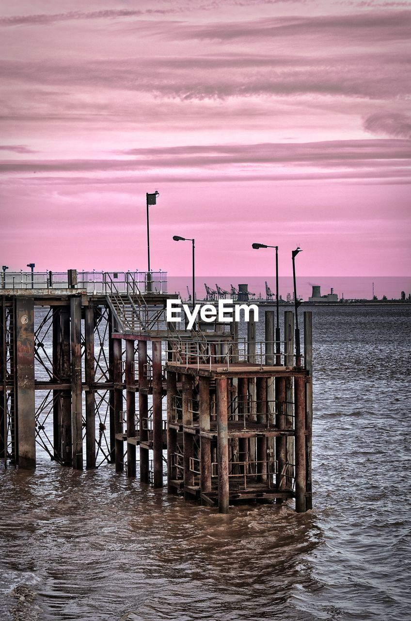 WOODEN POSTS ON PIER OVER SEA AGAINST SKY DURING SUNSET