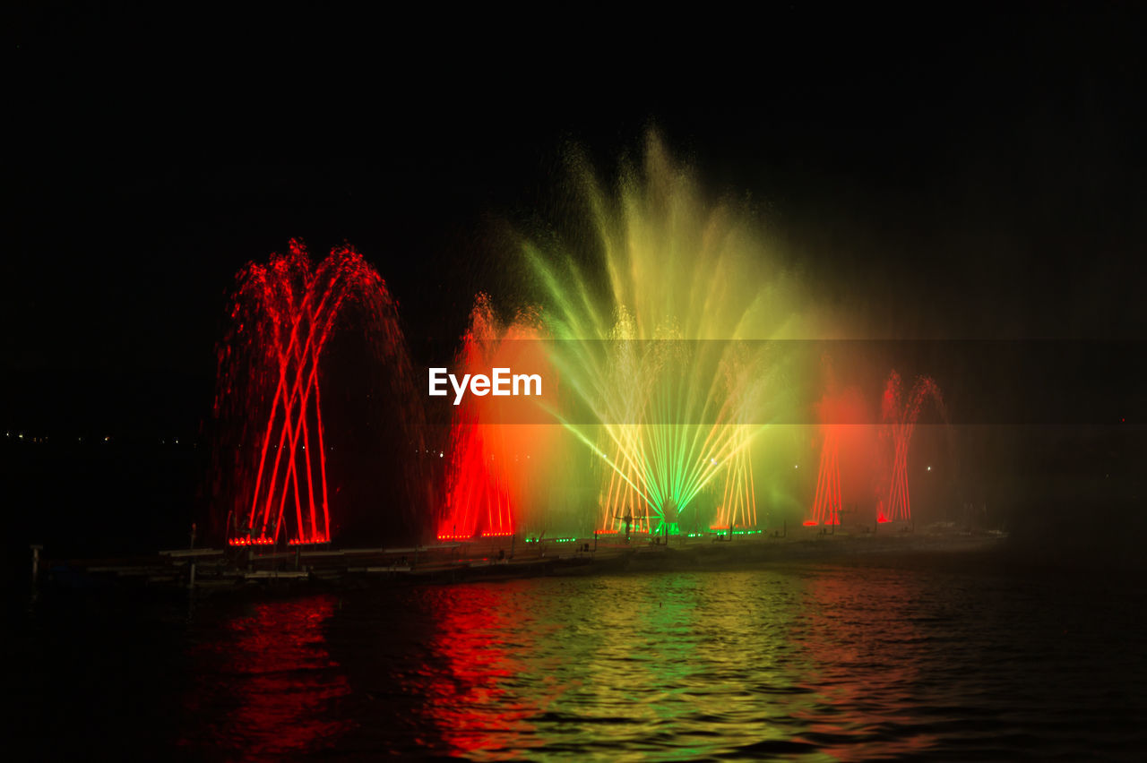 night, water, long exposure, illuminated, motion, red, waterfront, outdoors, sky, multi colored, built structure, no people, nature, architecture, power in nature, clear sky