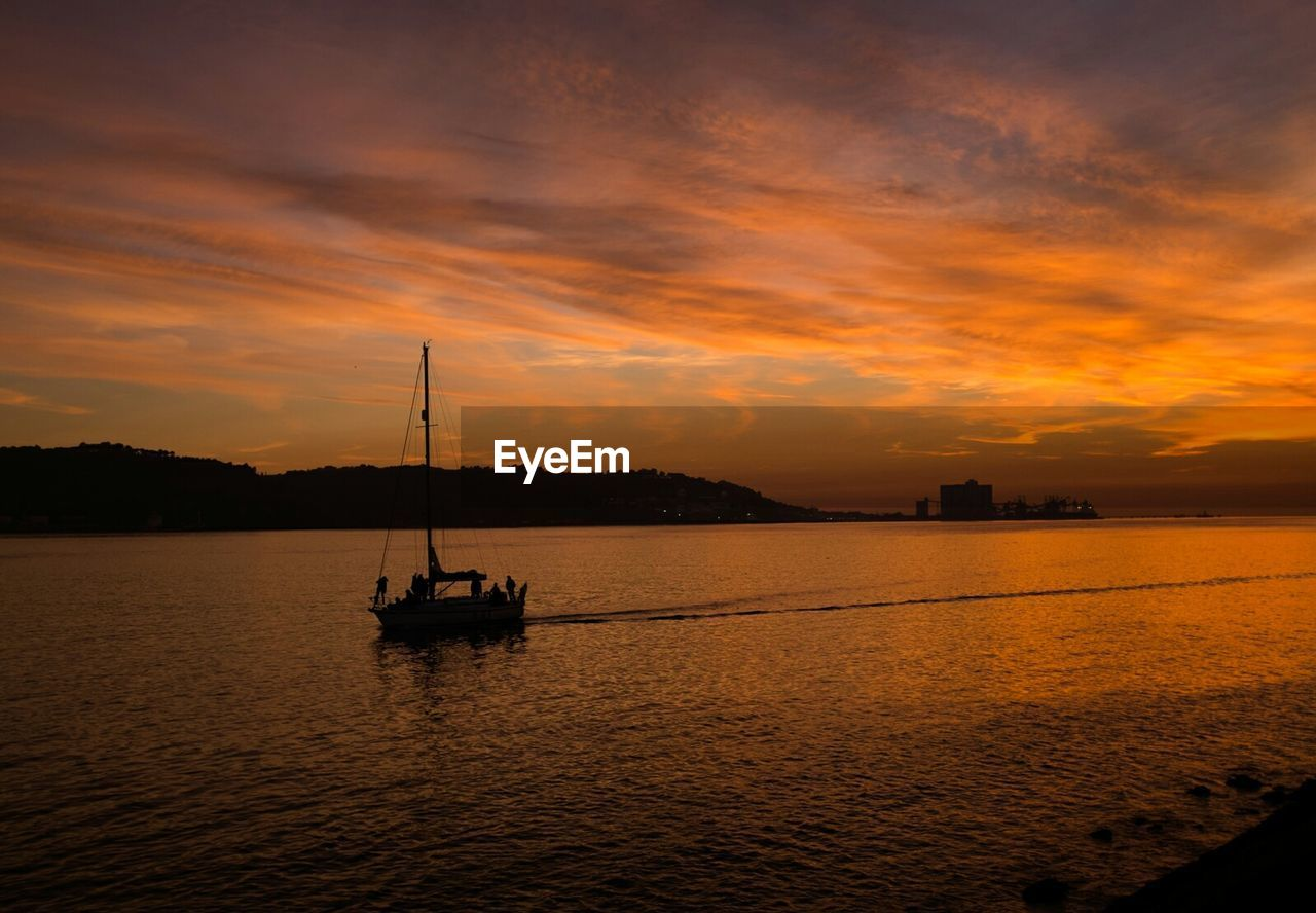 sunset, water, nautical vessel, orange color, sky, transportation, cloud - sky, boat, nature, beauty in nature, mode of transport, tranquility, scenics, sea, waterfront, silhouette, reflection, no people, outdoors, mast, moored, sailing