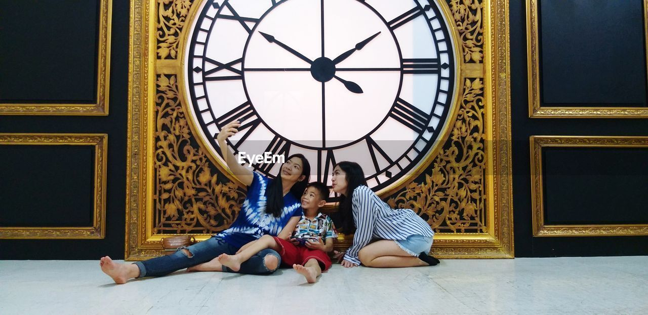 Full length of woman taking selfie with family while sitting on tiled floor against clock