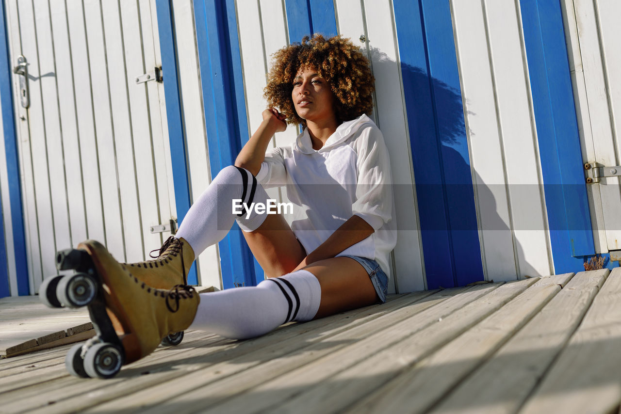 Young Woman With Roller Skates Sitting By Wall