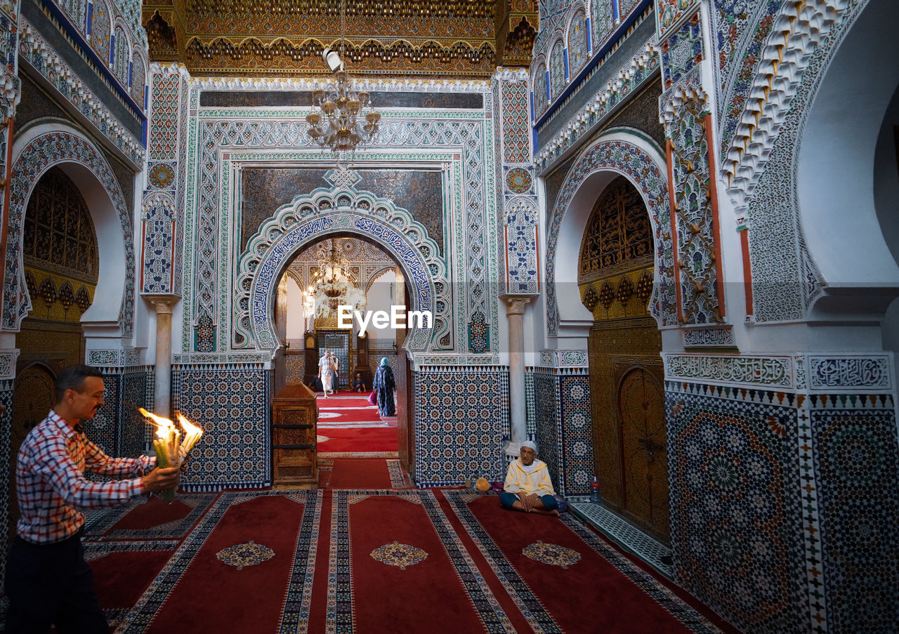 architecture, arch, built structure, religion, belief, spirituality, group of people, real people, building, place of worship, indoors, praying, lifestyles, men, illuminated, people, sitting, architectural column, ornate