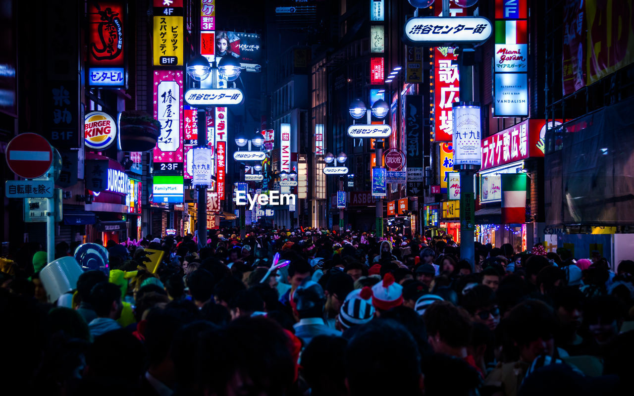 Crowd Amidst Illuminated Billboards On Buildings In City
