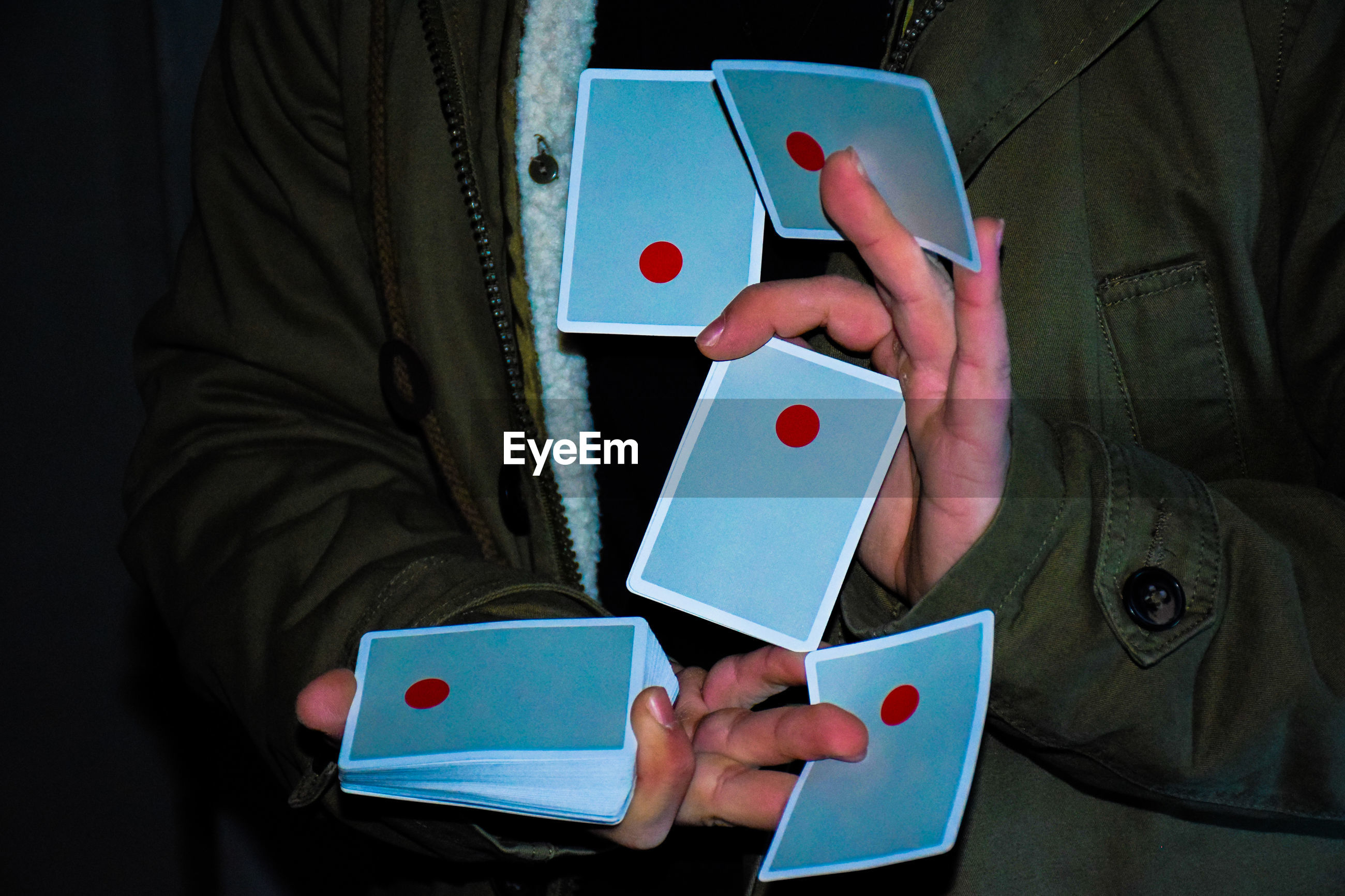 Midsection of illusionist holding cards