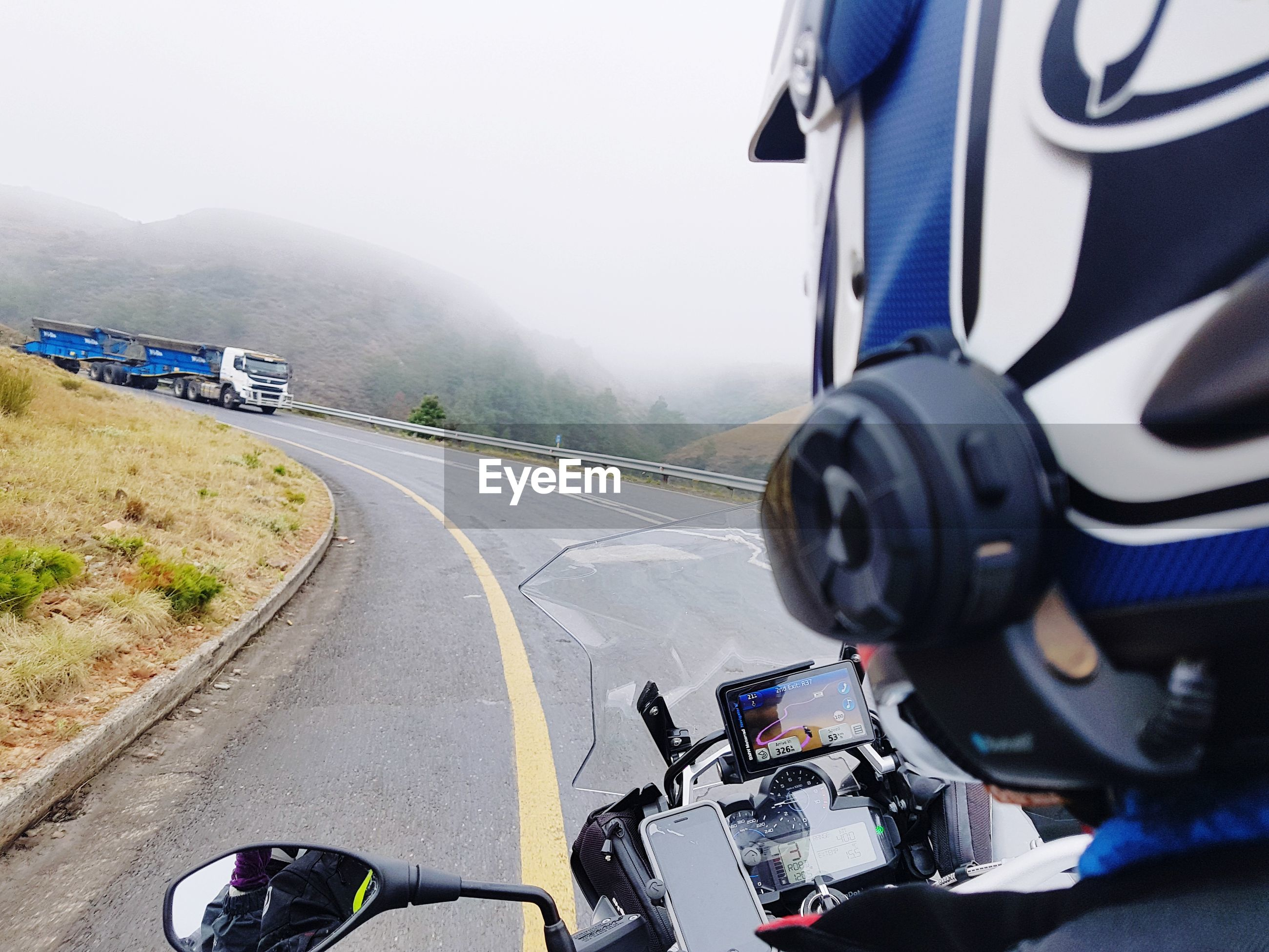 VIEW OF MAN RIDING MOTORCYCLE ON ROAD AGAINST SKY