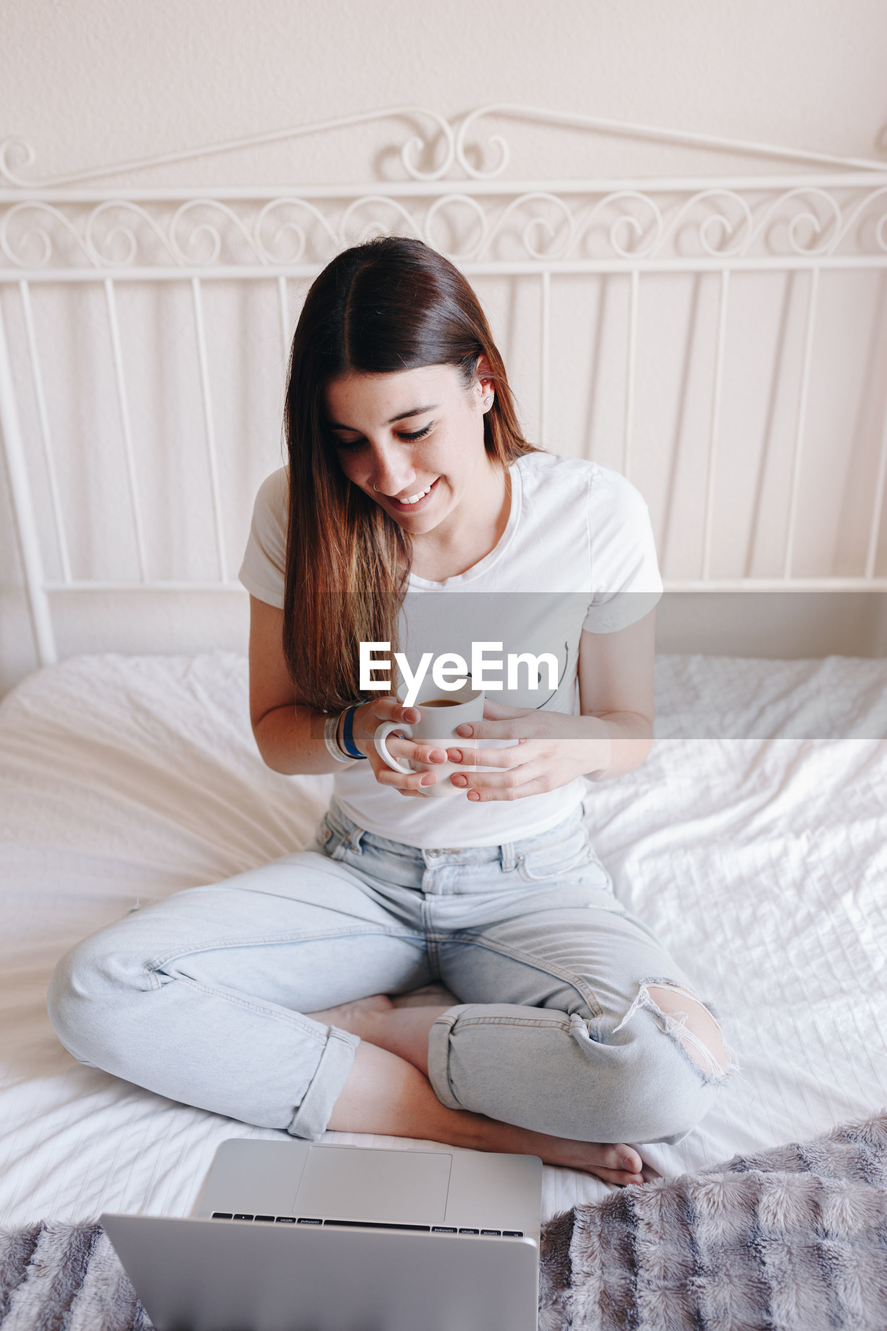 Young woman drinking coffee while using laptop on bed at home