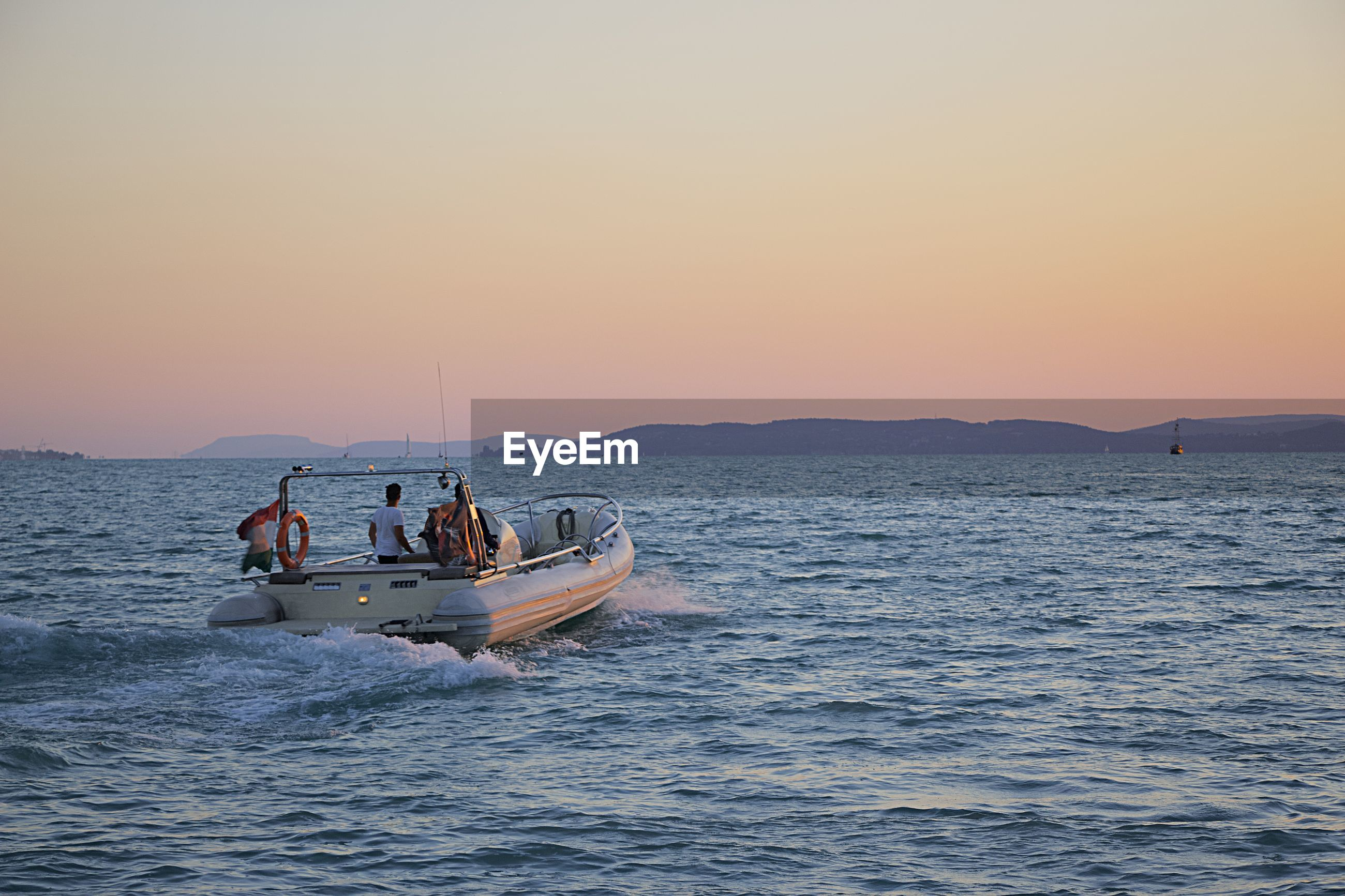 PEOPLE IN BOAT SAILING ON SEA AGAINST CLEAR SKY
