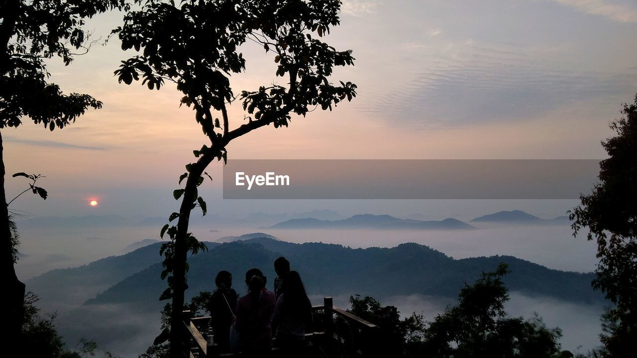 sky, tree, sunset, plant, mountain, beauty in nature, real people, group of people, silhouette, men, nature, scenics - nature, lifestyles, leisure activity, togetherness, cloud - sky, adult, women, people, tranquil scene, mountain range, outdoors, looking at view