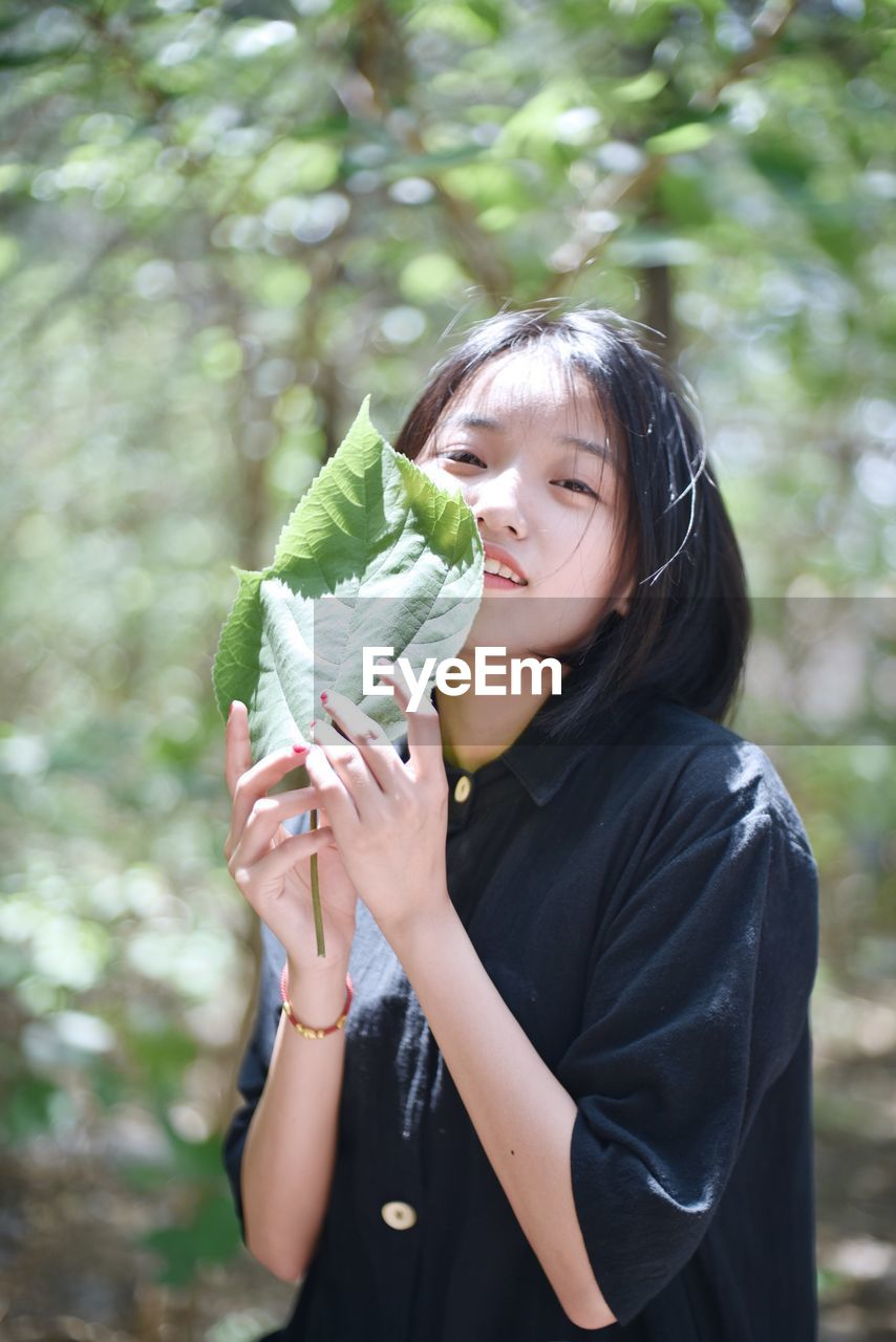 Portrait Of Woman Holding Leaves Against Tree