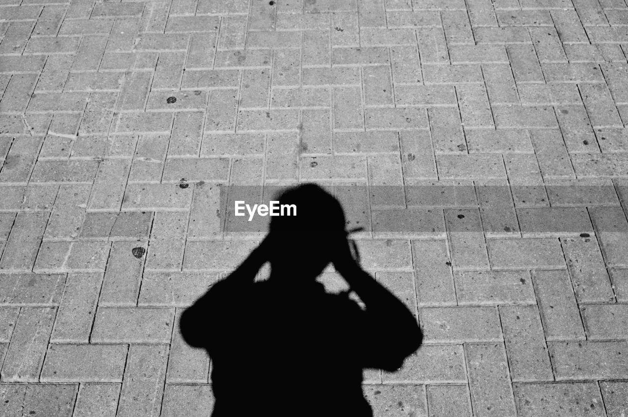 Shadow of man standing on cobblestone street