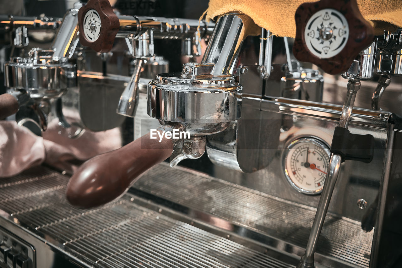 Close up of professional coffee machine. brown handles and chrome surfaces of coffee machine.