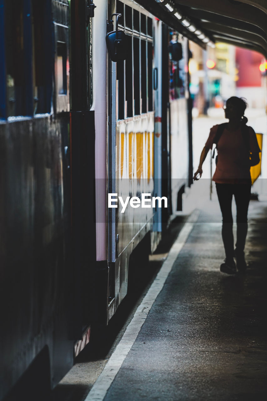 one person, architecture, real people, full length, standing, rear view, lifestyles, railroad station platform, illuminated, public transportation, men, rail transportation, casual clothing, railroad station, incidental people, transportation, walking, city, built structure