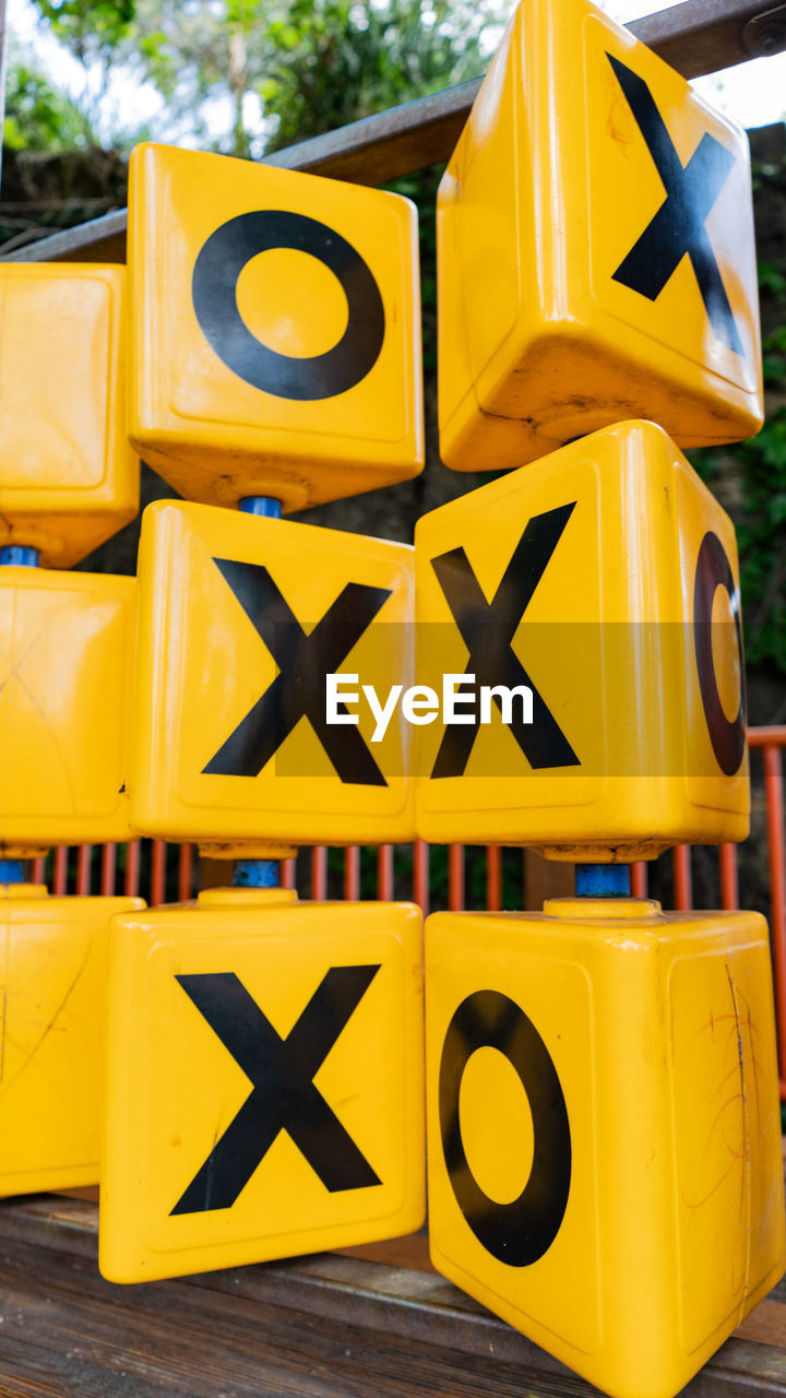 yellow, no people, communication, close-up, day, focus on foreground, large group of objects, construction industry, outdoors, sign, construction site, stack, still life, letter, retail, transportation, protection, container, capital letter, for sale