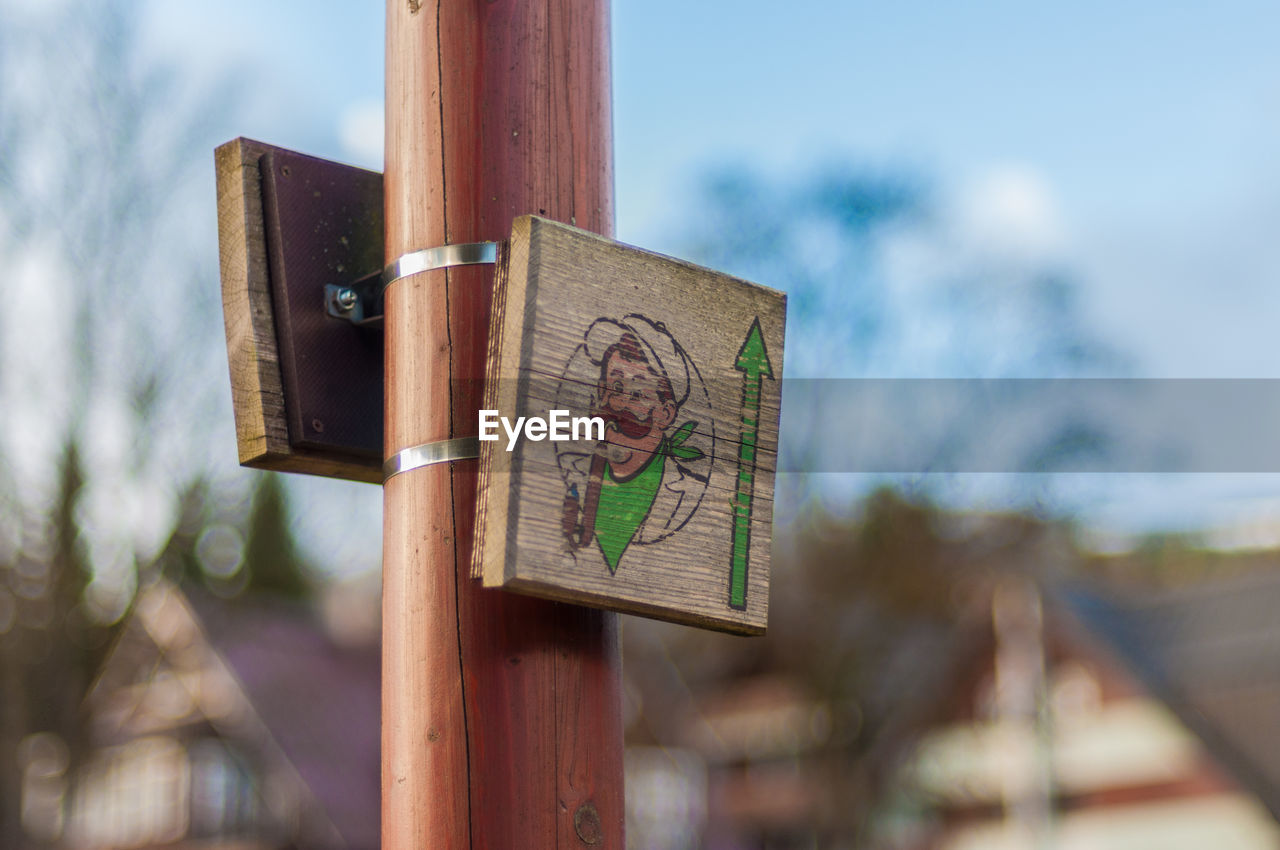 focus on foreground, communication, wood - material, text, day, no people, outdoors, tree, close-up, guidance, placard, childhood, nature, sky
