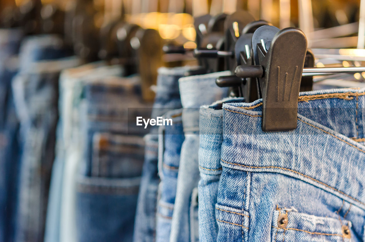 in a row, selective focus, indoors, textile, jeans, no people, hanging, close-up, metal, focus on foreground, denim, wood - material, still life, casual clothing, blue, clothing, large group of objects, day, for sale, absence, consumerism
