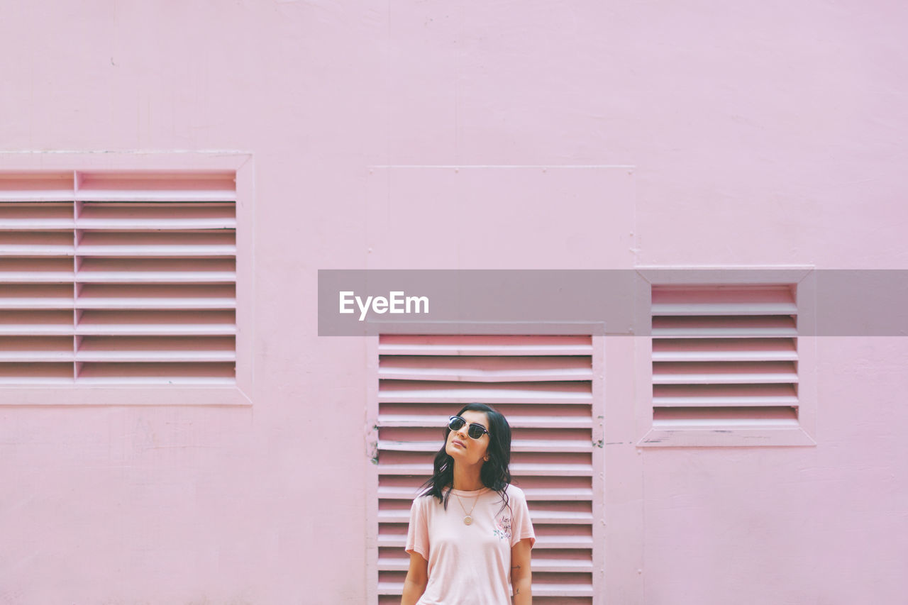 Woman with sunglasses standing against pink wall