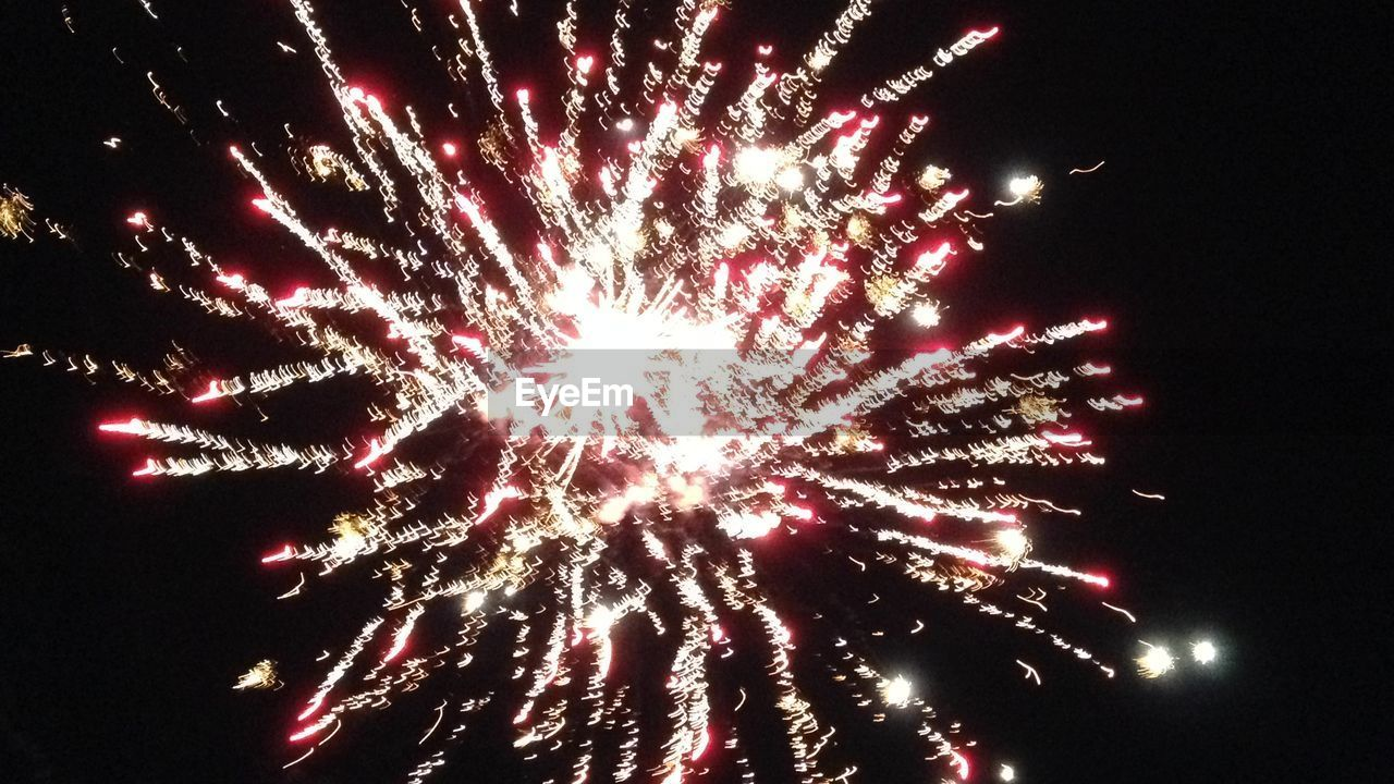 firework display, celebration, exploding, firework - man made object, event, arts culture and entertainment, sparks, low angle view, night, long exposure, glowing, smoke - physical structure, motion, blurred motion, multi colored, no people, cultures, outdoors, celebration event, firework, illuminated, sky, clear sky