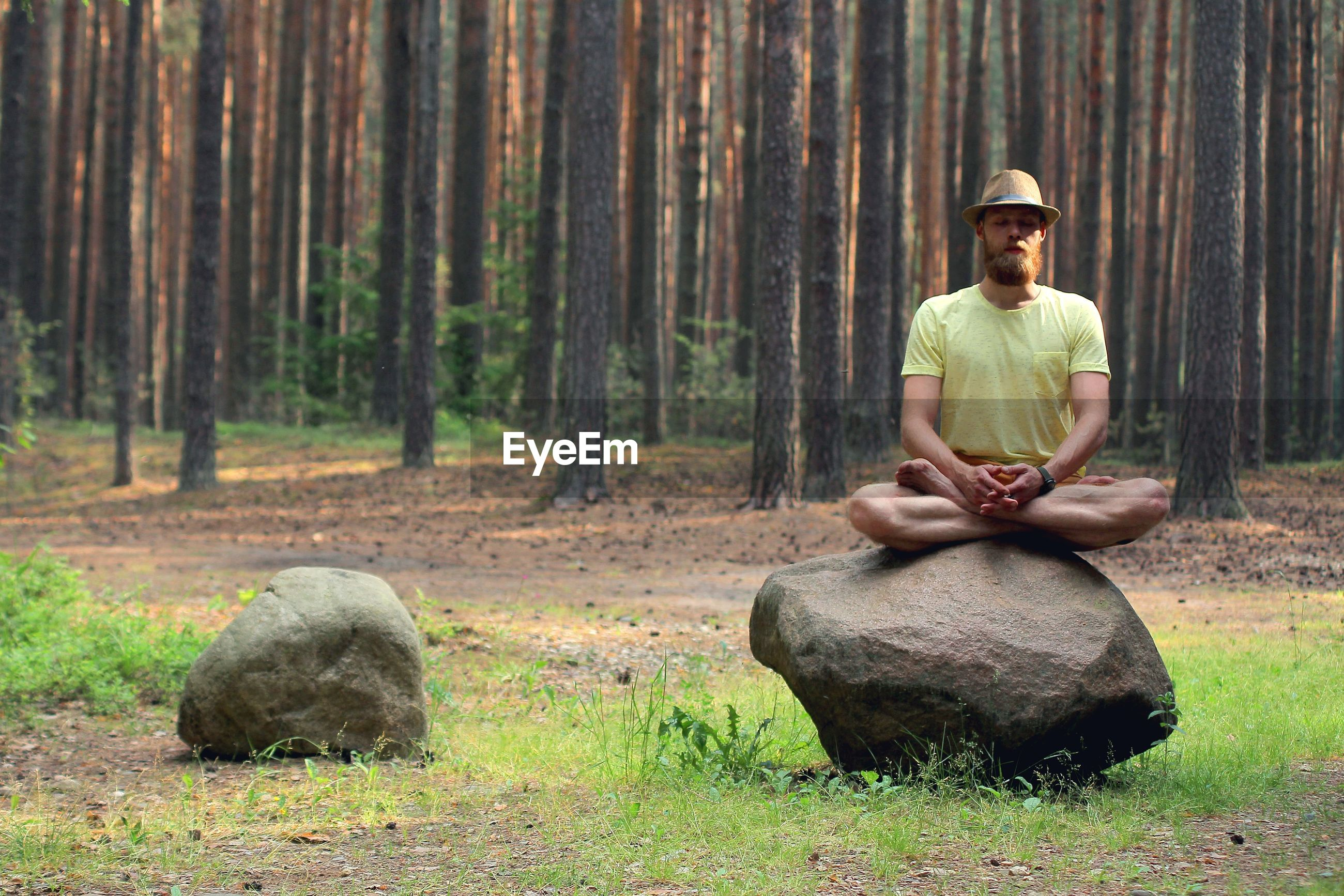 Man doing yoga on rock at forest