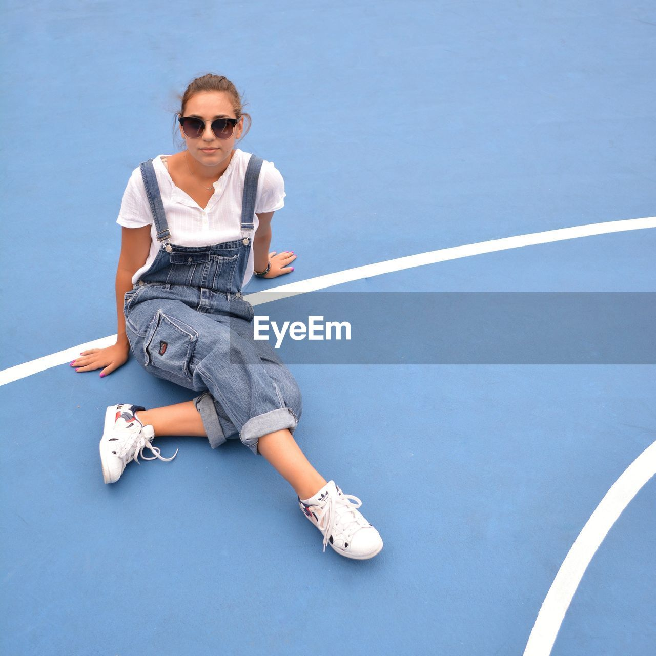 High Angle Portrait Of Young Woman Wearing Sunglasses Sitting On Blue Floor