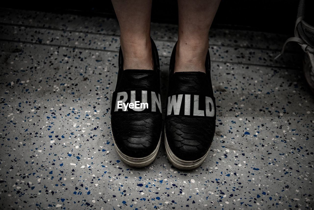 Low Section Of Man Wearing Shoes With Text On Floor