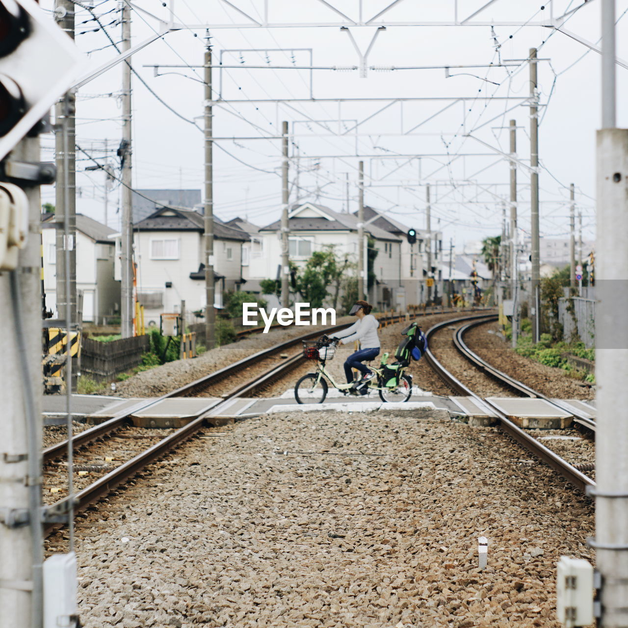 transportation, rail transportation, track, mode of transportation, railroad track, bicycle, architecture, cable, land vehicle, built structure, men, electricity pylon, building exterior, day, real people, electricity, power line, nature, connection, city, riding, outdoors, power supply