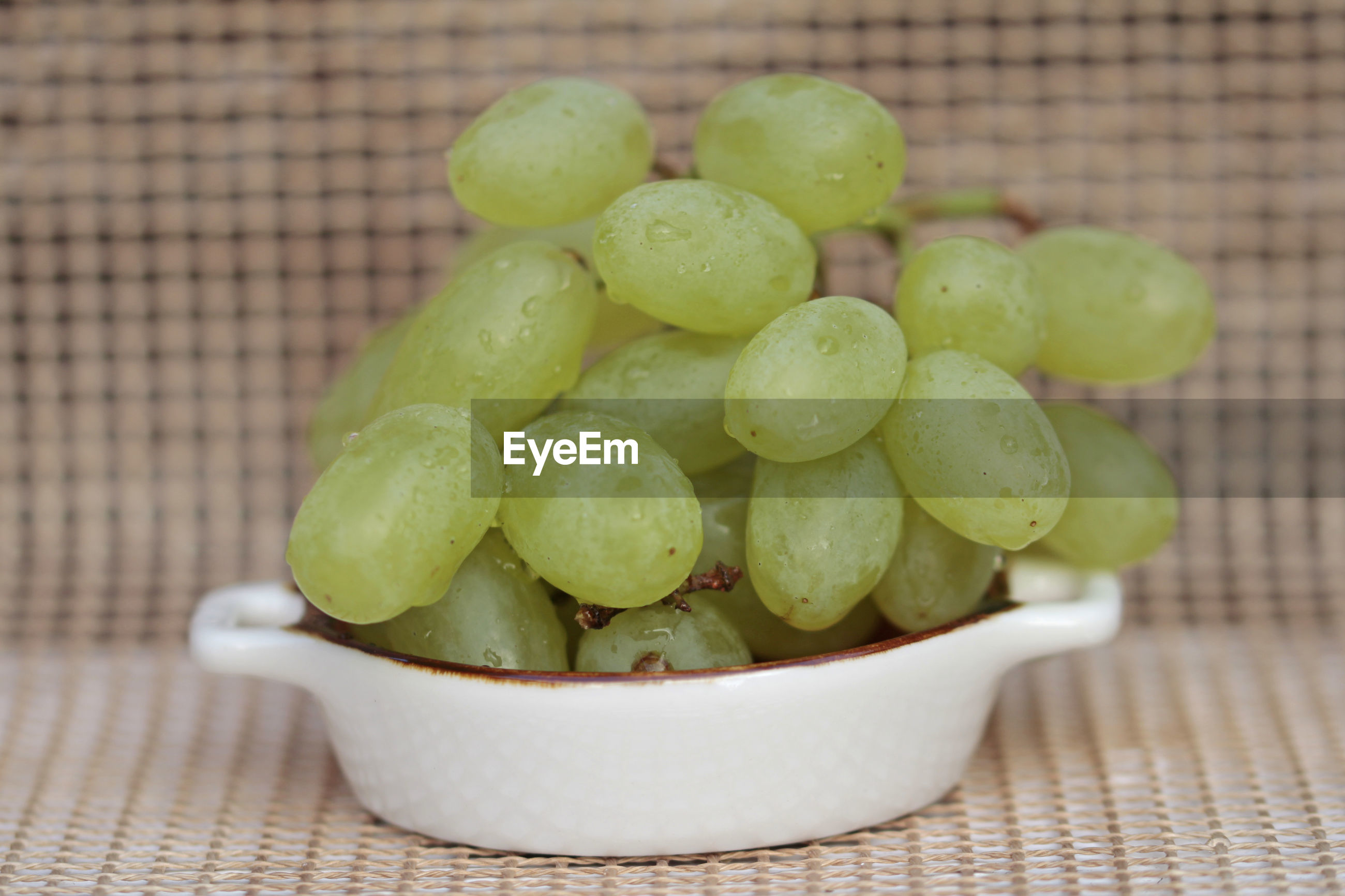 CLOSE-UP OF GRAPES IN CONTAINER ON TABLE