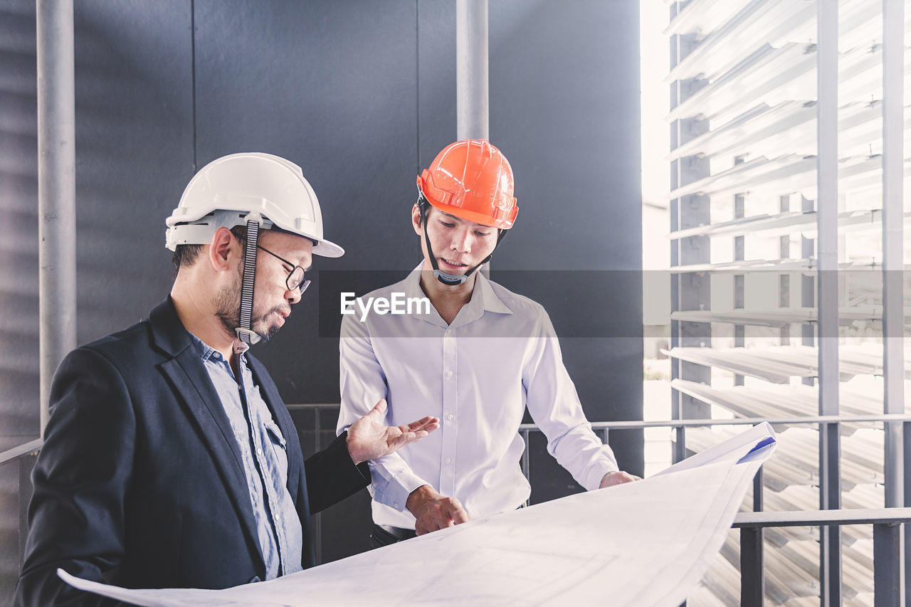 helmet, hardhat, headwear, occupation, cooperation, construction industry, teamwork, business, working, men, hat, males, architect, coworker, design professional, industry, standing, safety, indoors, two people, mature adult, mature men, blueprint, planning, explaining