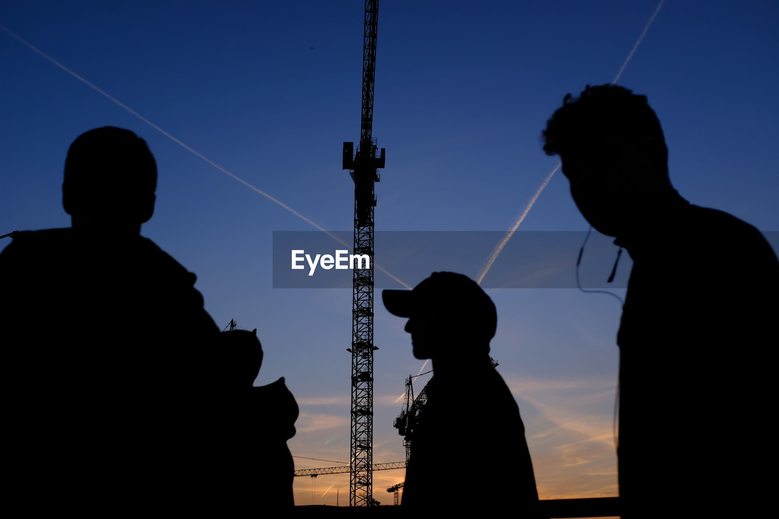 Silhouette people standing against crane during sunset
