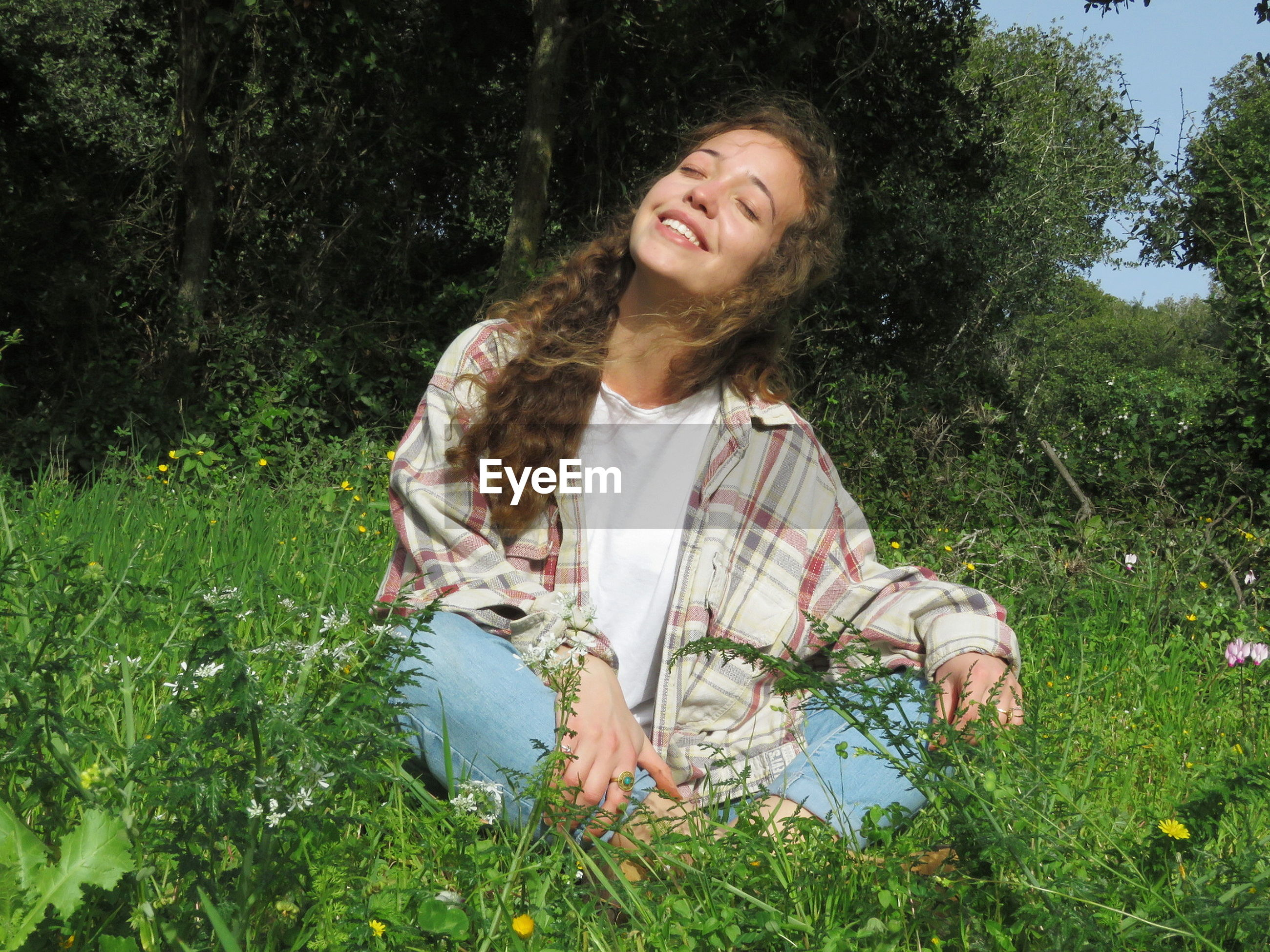 Smiling young woman sitting on grassy field