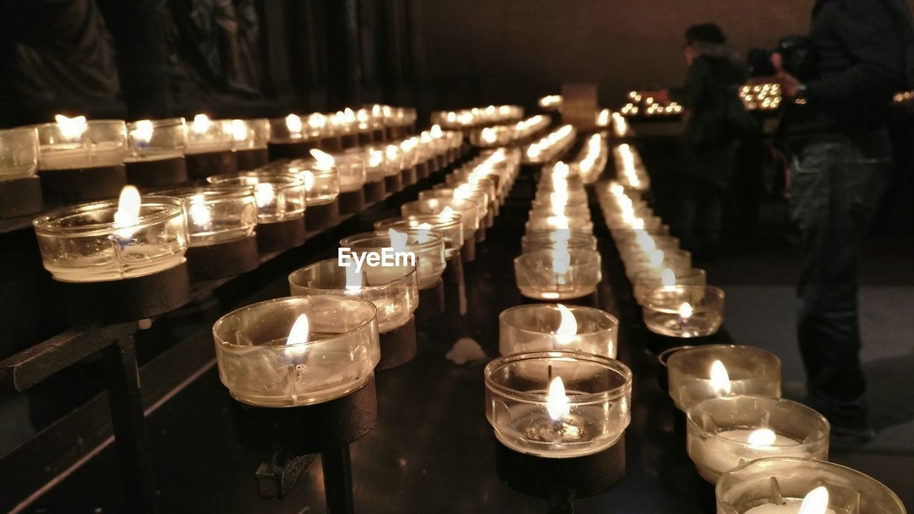 candle, flame, burning, heat - temperature, illuminated, tea light, religion, glowing, spirituality, in a row, large group of objects, indoors, focus on foreground, place of worship, no people, table, arrangement, close-up