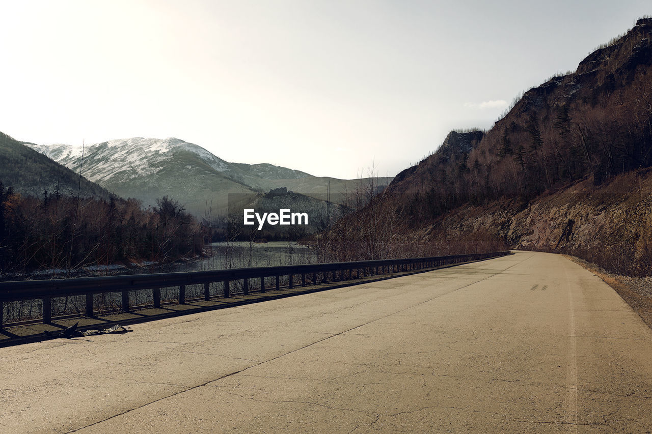 mountain, sky, road, transportation, direction, the way forward, nature, no people, mountain range, beauty in nature, environment, tranquil scene, tranquility, diminishing perspective, scenics - nature, day, outdoors, non-urban scene, landscape, leadership, crash barrier