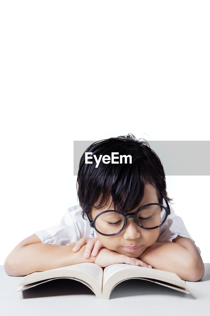 Boy Wearing Eyeglasses Studying On Table Against White Background
