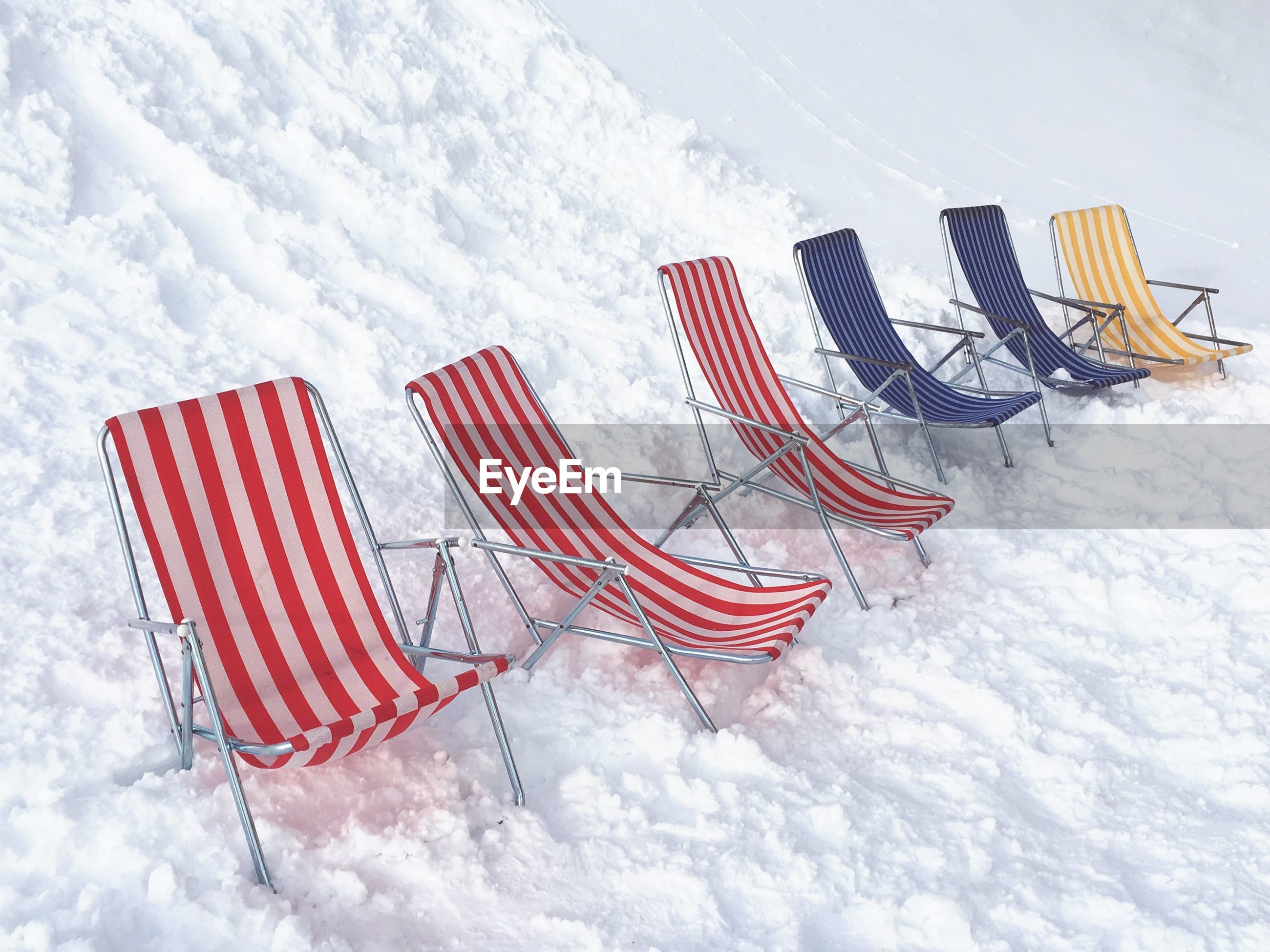 Row of relaxing chairs on snow