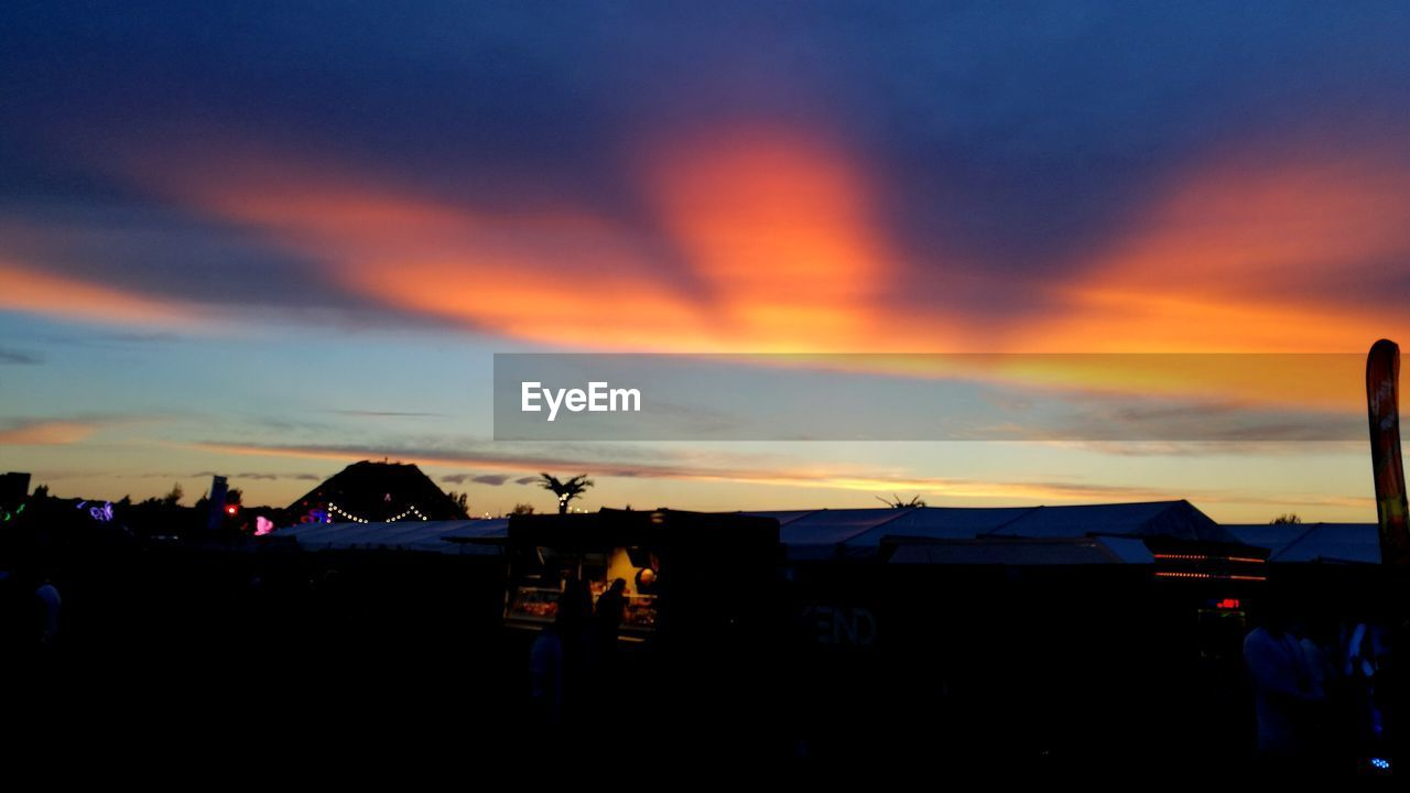 sunset, silhouette, orange color, sky, built structure, cloud - sky, nature, building exterior, outdoors, real people, beauty in nature, architecture, one person, technology, day, people