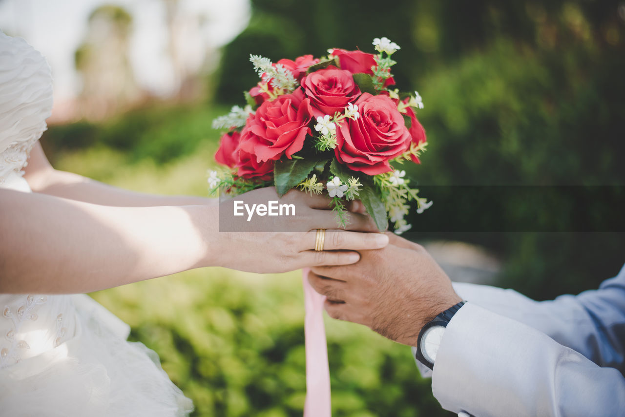 Midsection Of Groom Giving Bouquet To Bride During Wedding Ceremony
