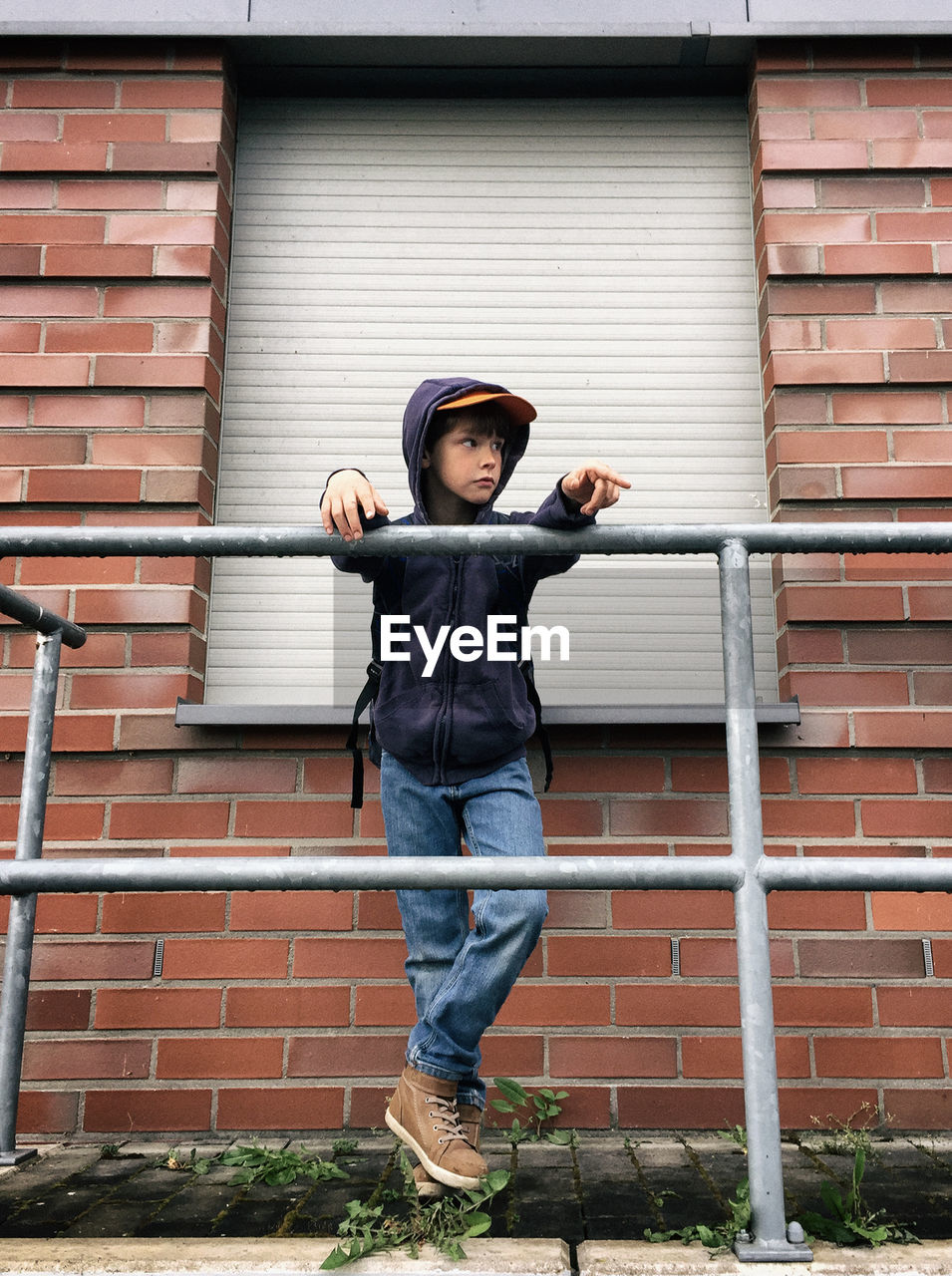 Low angle view of boy looking away while standing by railing against brick wall