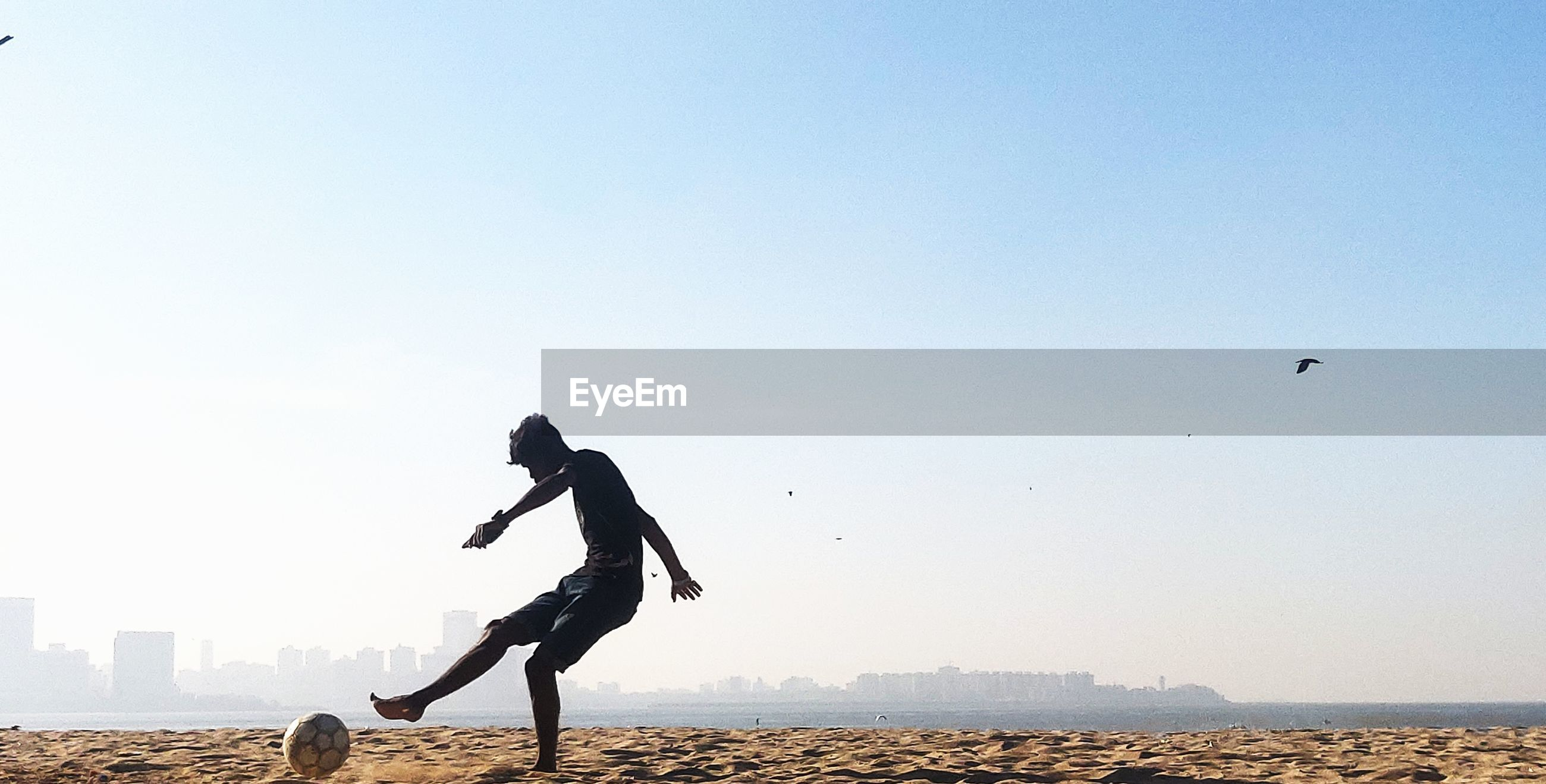Teenage boy playing soccer at beach against clear sky