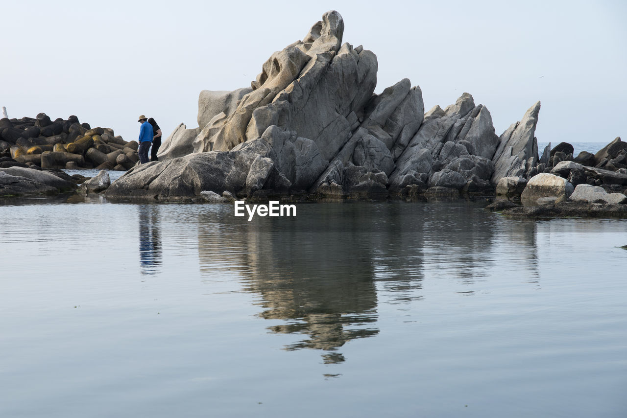 Reflection Of Rocks In Sea Against Clear Sky