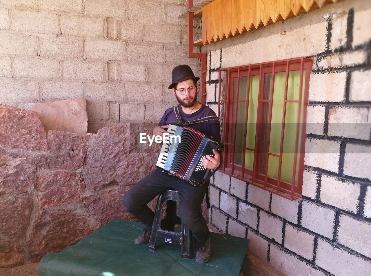 brick wall, front view, musical instrument, music, full length, house, building exterior, architecture, looking at camera, built structure, accordion, outdoors, one person, musician, lifestyles, day, portrait, young adult, only men, adult, people, adults only