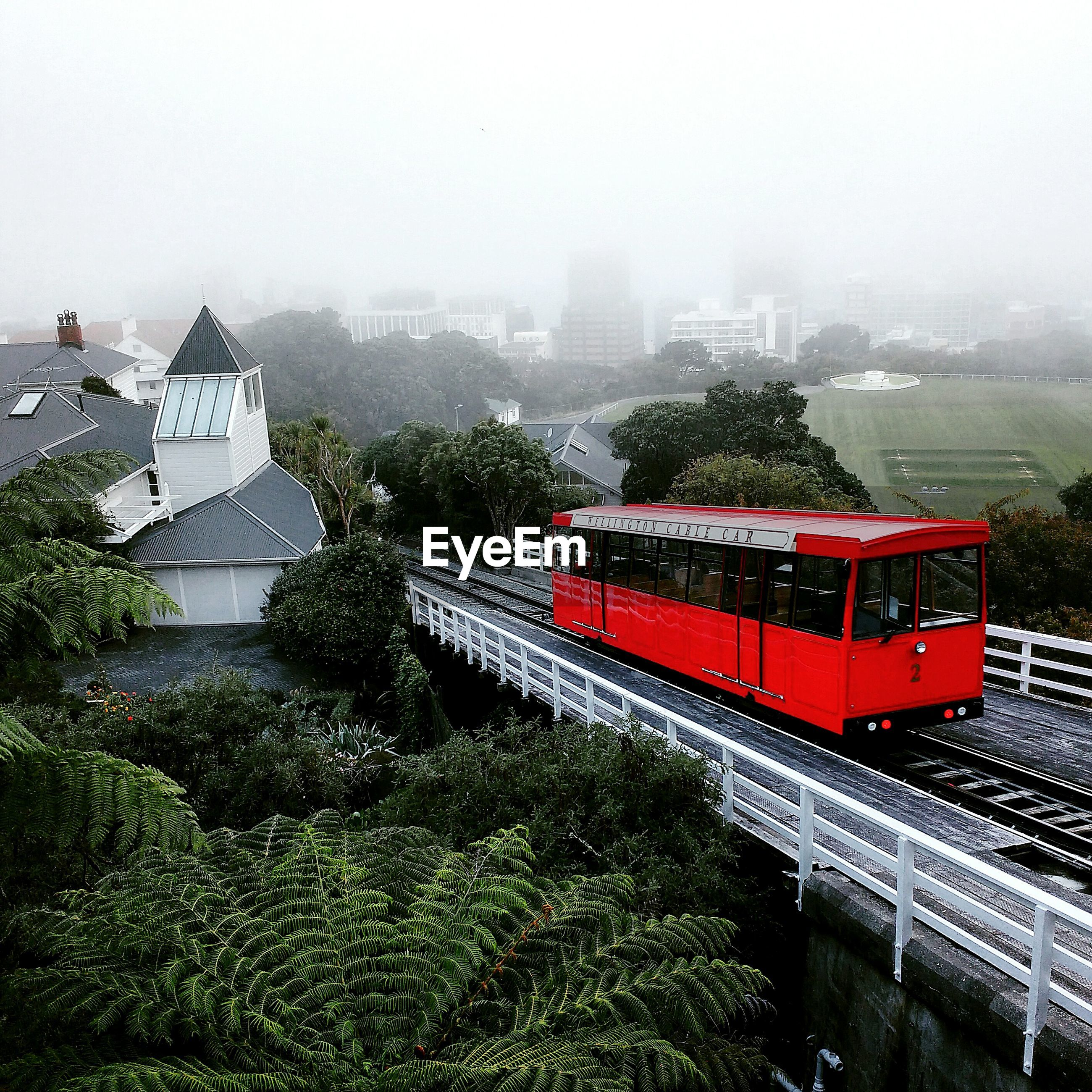 HIGH ANGLE VIEW OF TRAIN AMIDST TREES IN CITY