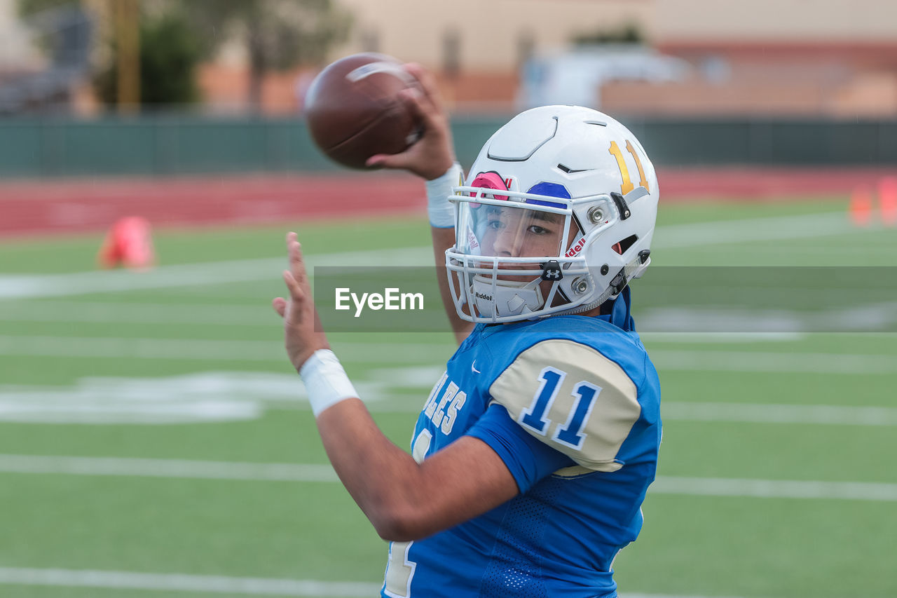 sport, helmet, headwear, focus on foreground, one person, american football - sport, sports helmet, american football - ball, real people, child, sports equipment, childhood, clothing, side view, men, waist up, leisure activity, athlete, sports clothing