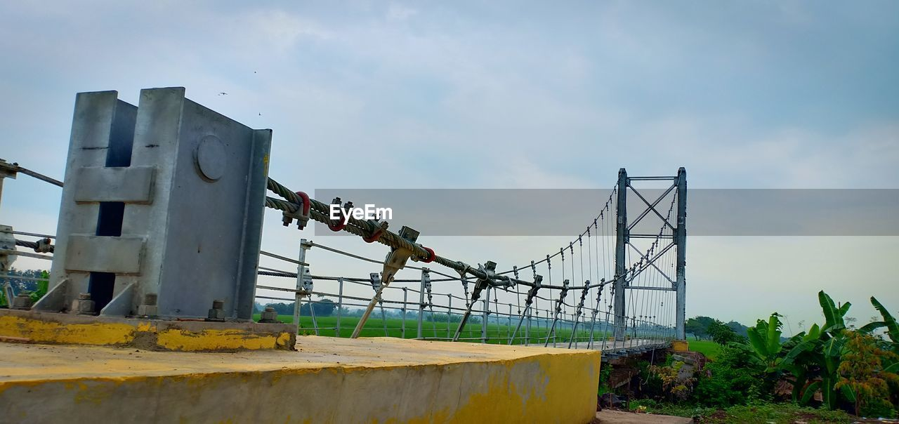 sky, cloud - sky, built structure, nature, day, architecture, metal, no people, outdoors, plant, low angle view, industry, fence, barrier, boundary, machinery, building exterior, damaged, factory, connection, industrial equipment