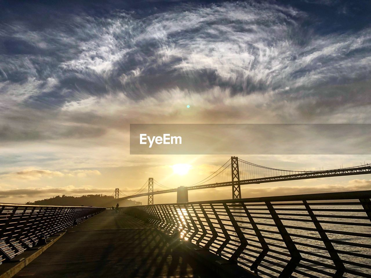 sky, cloud - sky, bridge, sunlight, architecture, connection, sun, nature, built structure, bridge - man made structure, sunset, outdoors, beauty in nature, no people, railing, scenics - nature, tranquility, lens flare, sunbeam, water, bright
