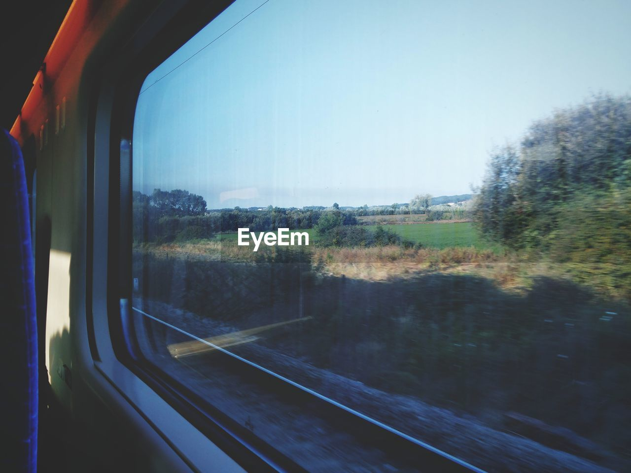 transportation, vehicle interior, window, journey, landscape, train - vehicle, mode of transport, rail transportation, tree, nature, public transportation, travel, no people, land vehicle, day, clear sky, beauty in nature, scenics, sky, road trip, outdoors, grass