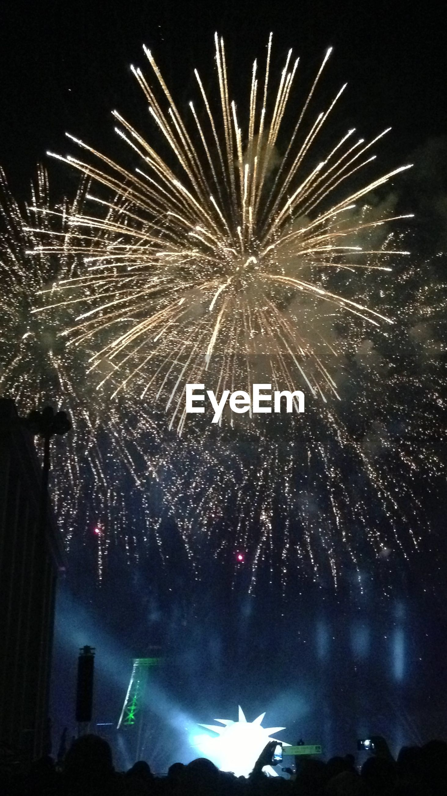 Low angle view of illuminated fireworks by eiffel tower against sky at night