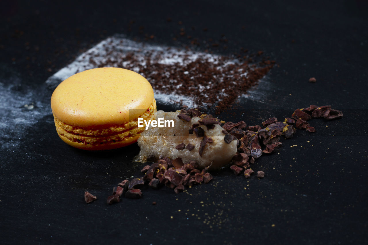 Close-Up Of Macaroon With Ground Coffee On Table
