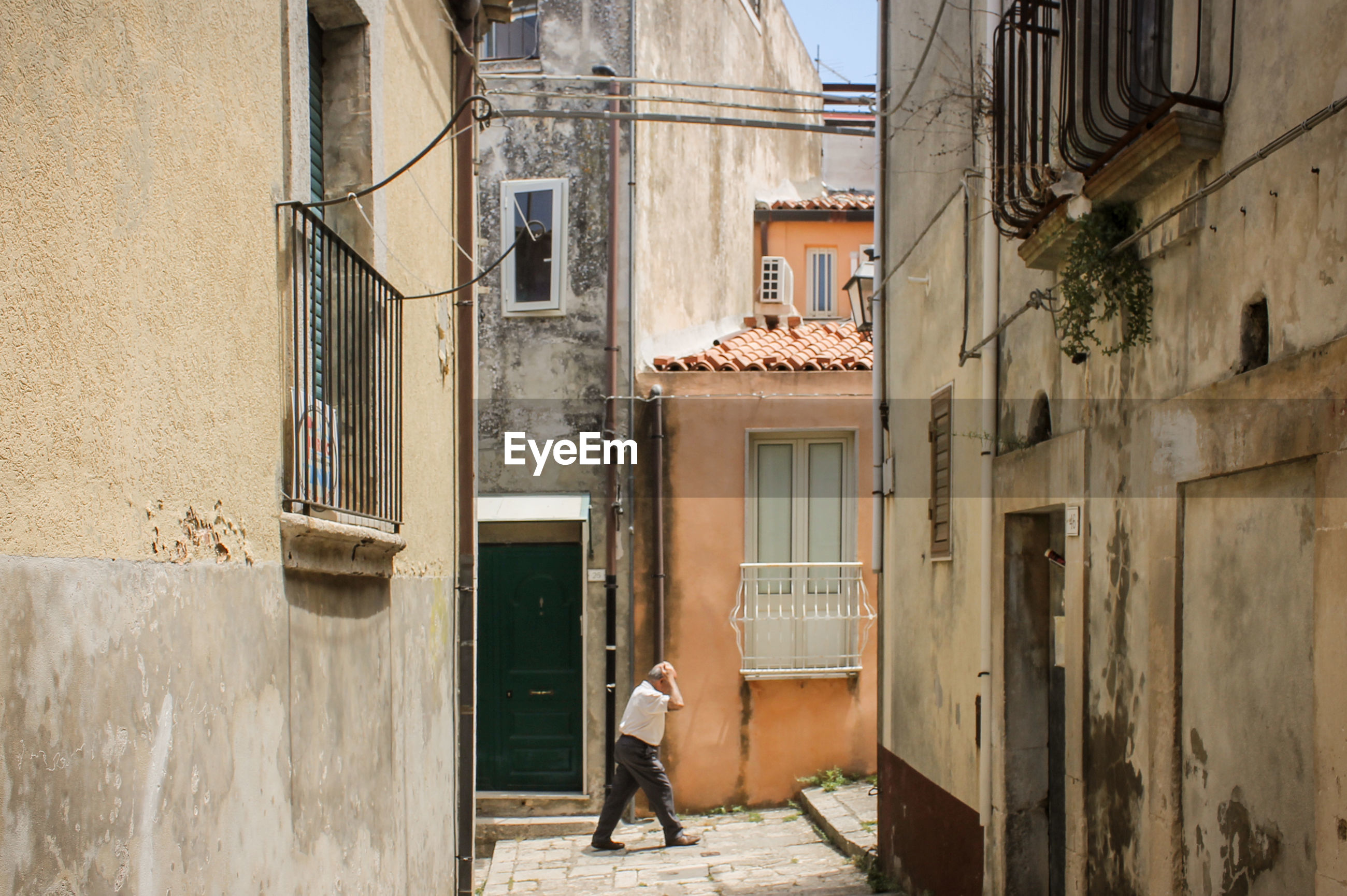 REAR VIEW OF WOMAN WALKING ON STREET AGAINST BUILDINGS
