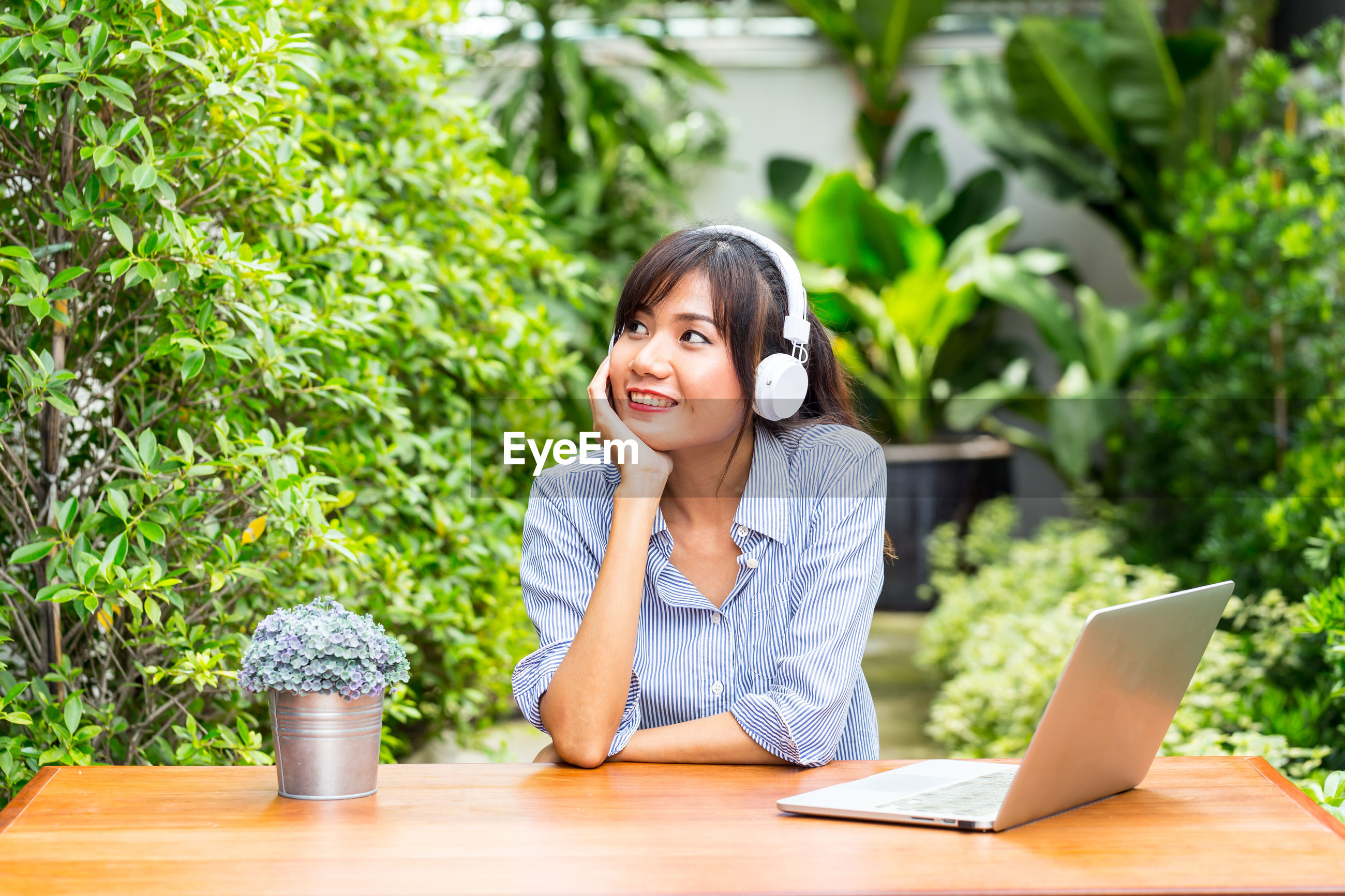Smiling young woman listening to music while sitting at table against plants